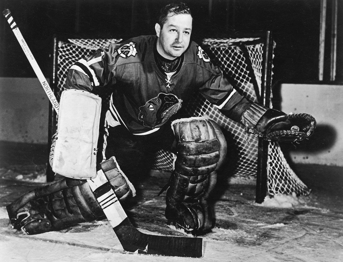 "One of the greatest of all time, ""Mr. Goalie"" spent 10 years between Chicago's pipes, earning eight All-Star nods, posting a 275-229-106 mark with 51 shutouts, and backstopping the Blackhawks' 1961 Stanley Cup championship that ended a 23-year drought for the franchise. A forerunner of the butterfly style, he was also well-known for getting sick to his stomach before games. Perhaps his most impressive feat was playing 502 consecutive regular season games, and 50 more in the playoffs, without a facemask. A back injury caused him to leave a game against Boston on November 8, 1963, thus ending his remarkable run. He was inducted into the Hockey Hall of Fame in 1975."