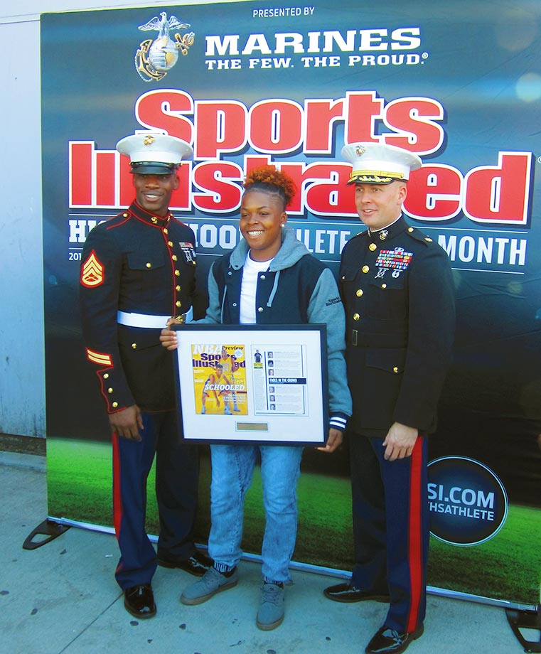 SI High School Athlete of the Month Nia Toliver is flanked by Sgt Moore Man and Major James Dollard as she holds her framed issue of Sports Illustrated.