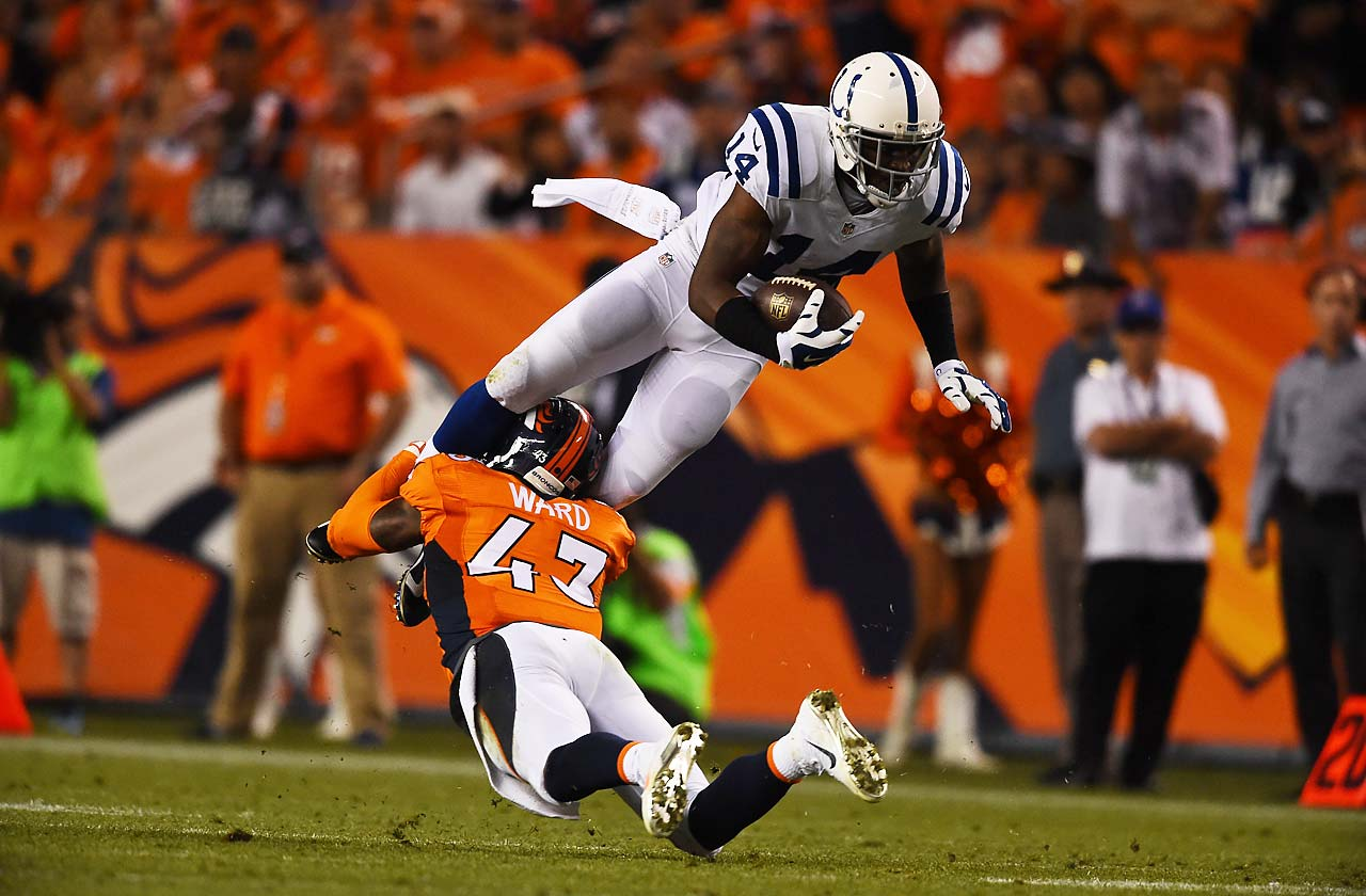 Wide receiver Hakeem Nicks of the Indianapolis Colts leaps over and is tackled by strong safety T.J. Ward of the Denver Broncos.