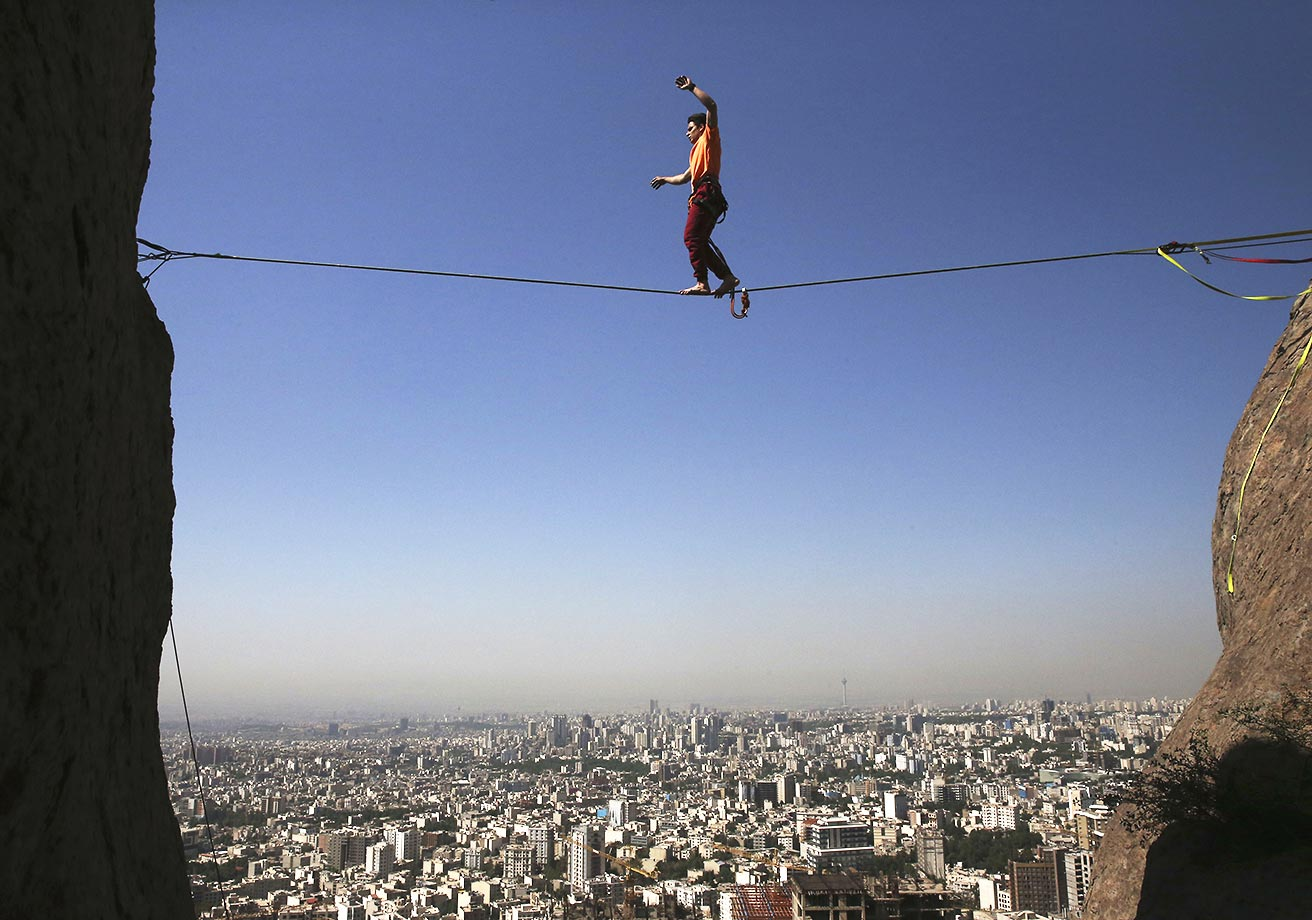 Hamed Heidari walks across a slackline anchored between two rocks in the mountains overlooking Tehran, Iran.