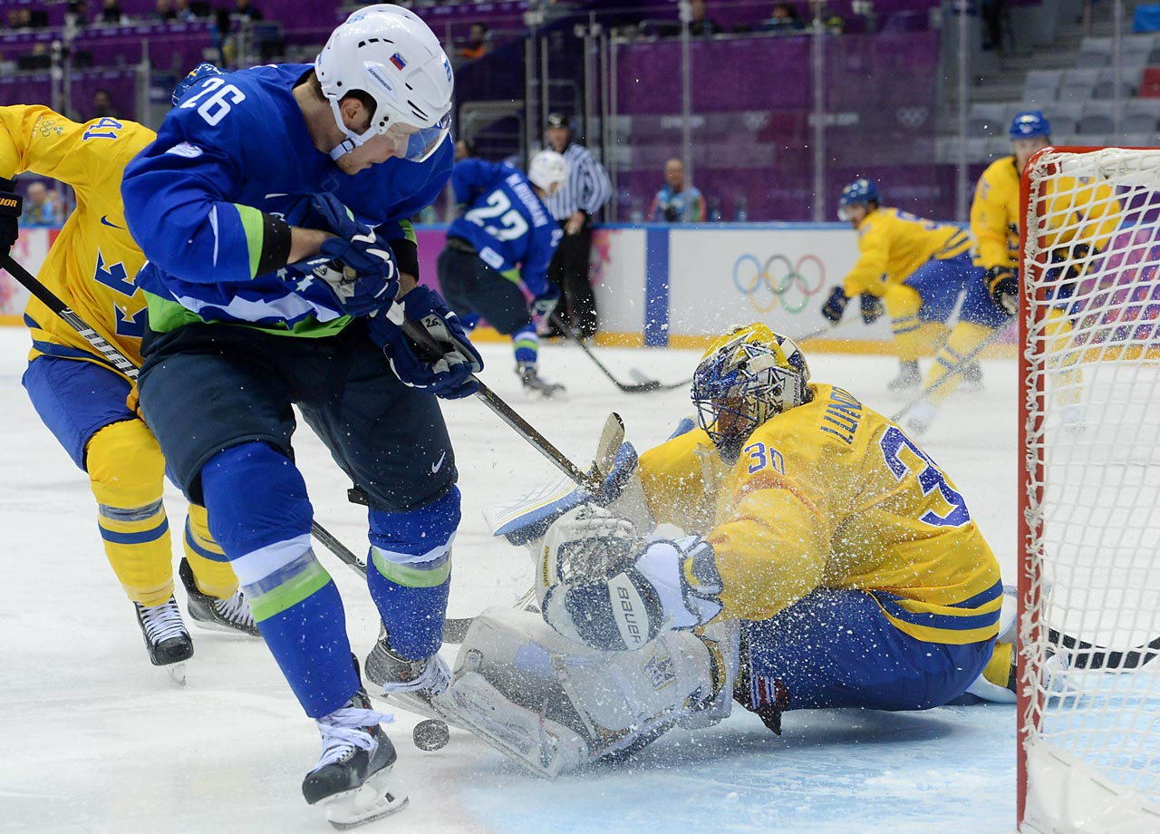 Goaltender Henrik Lundqvist of Sweden makes a save on Slovenian forward Jan Urbas during a quarterfinal game between the two countries. Sweden won handily, 5-0.