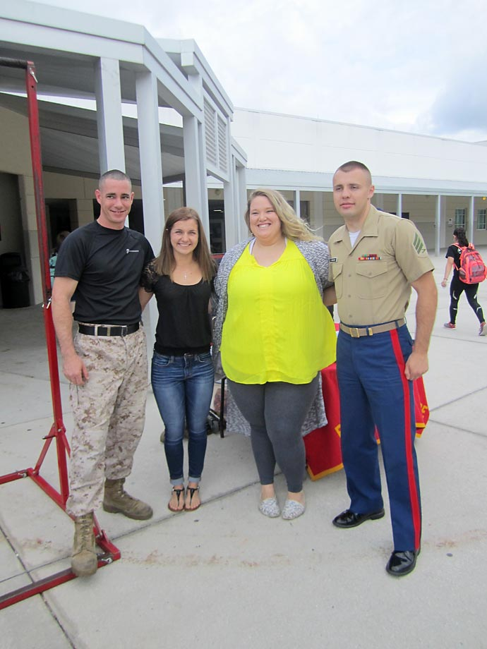 Representatives of the U.S. Marine Corps flank lifters Savannah Braud and Holley Mangold.