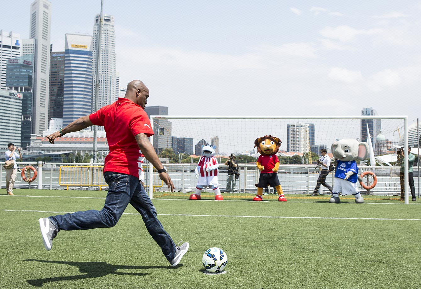 Ian Wright, former Arsenal player, takes a penalty kick against the football mascots of Everton, Stoke and Singapore during the Ticket Launch for the Barclay's Asia Trophy 2015 in Singapore.
