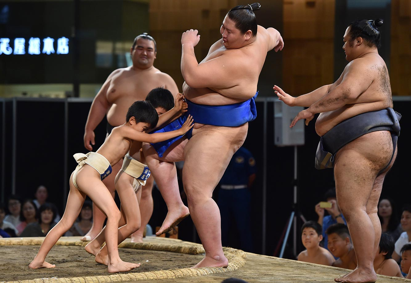 Junior sumo wrestlers push professional sumo wrestler Ichinojo out of the ring during an exhibition in Tokyo.