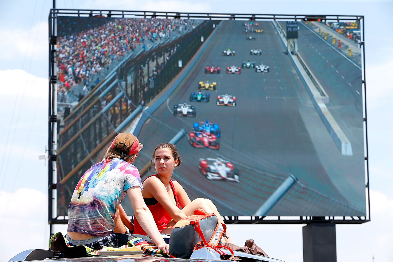 Fans sit atop their car to watch the race on a big screen TV.