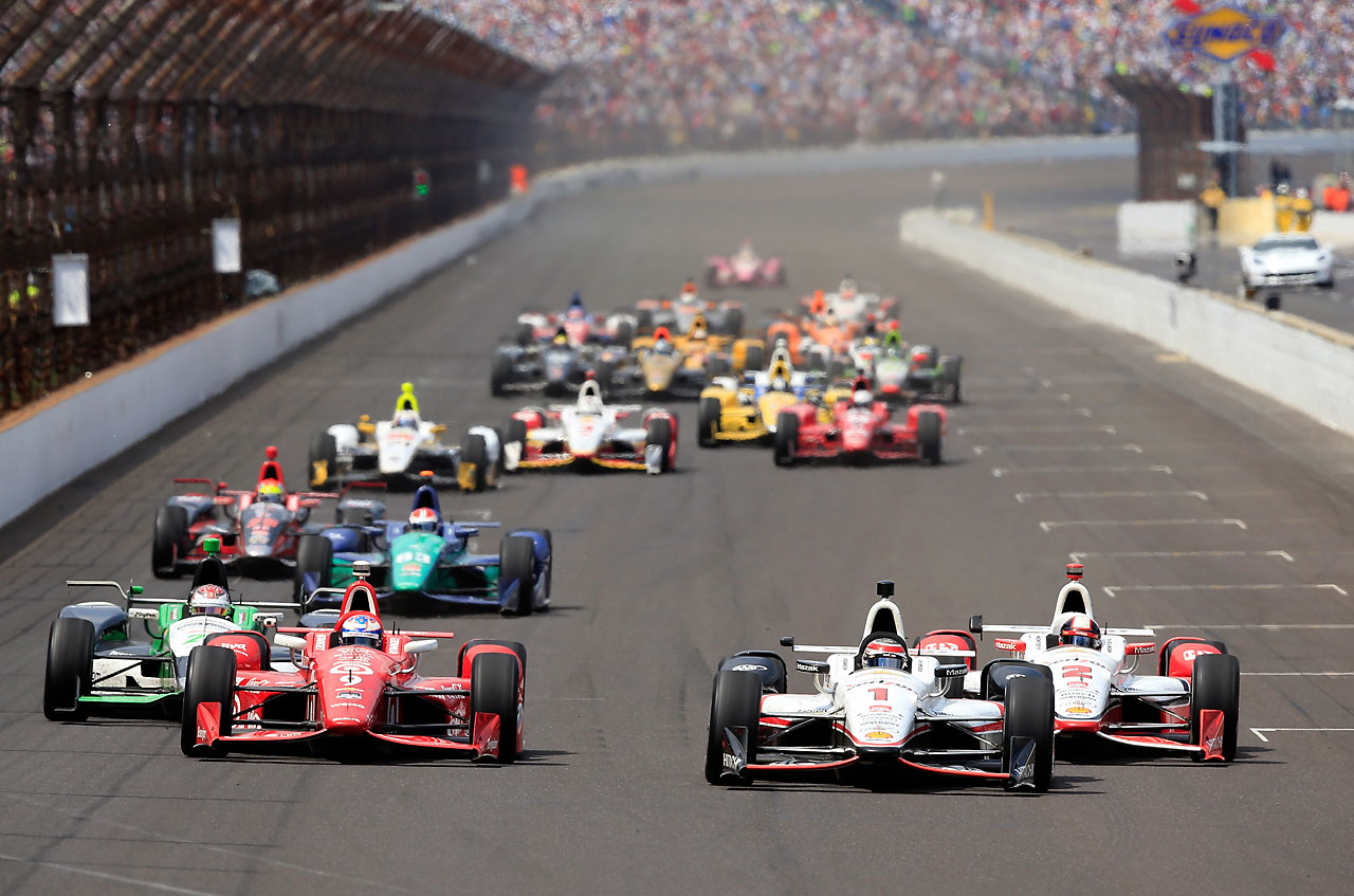 Scott Dixon of Australia races alongside Juan Pablo Montoya and Will Power after a restart.
