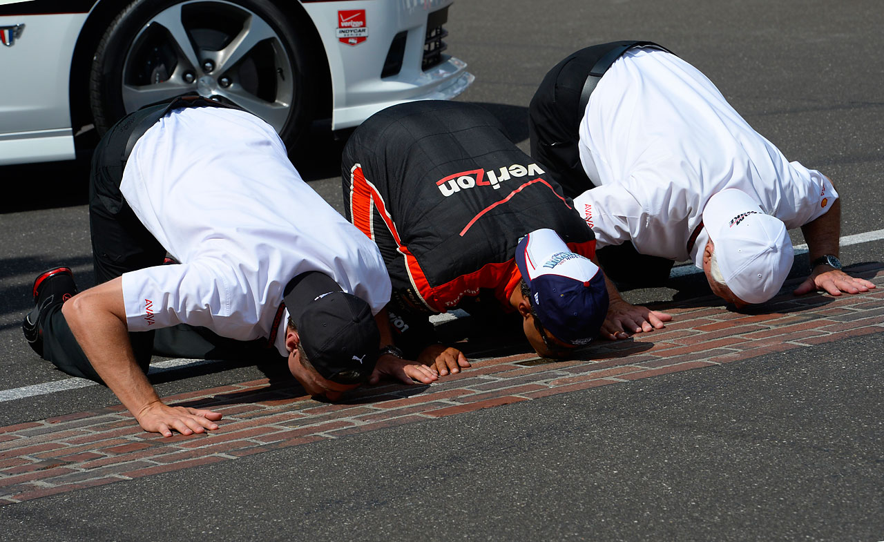 Tim Cindrik, Team Penske president, Juan Pablo Montoya and Roger Penske, owner of Team Penske, kiss the bricks after winning the Indianapolis 500.
