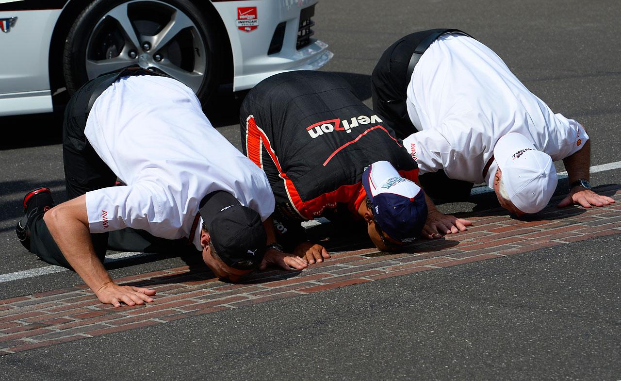 Tim Cindrik, Team Penske president, Juan Pablo Montoya and Roger Penske, owner of Team Penske, kiss the bricks after winning the Indianapolis 500.