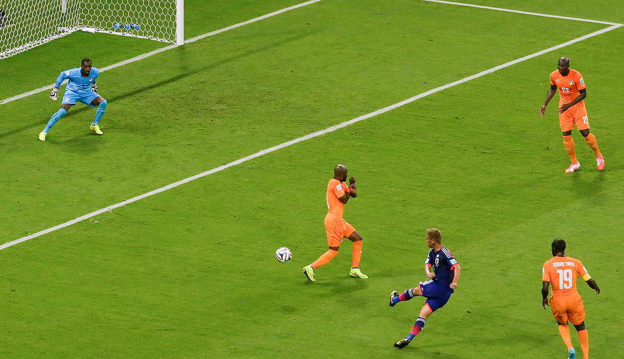 Japan's Keisuke Honda, second from right, scores the opening goal during the group C World Cup soccer match between Ivory Coast and Japan at the Arena Pernambuco in Recife, Brazil, on June 14.