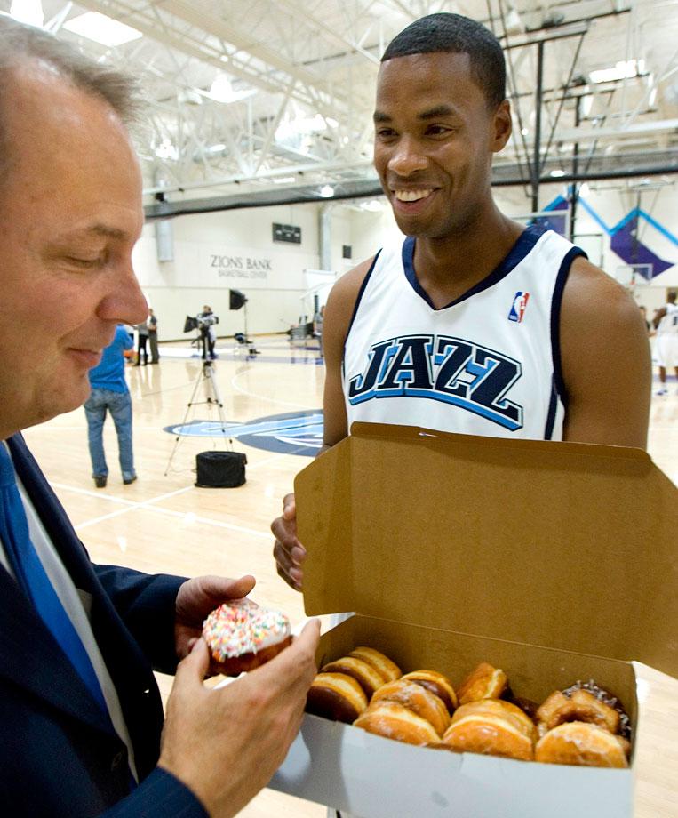 Utah Jazz center Jarron Collins offers team president Randy Rigby a doughnut during media day on Sept. 29, 2008 in Salt Lake City.