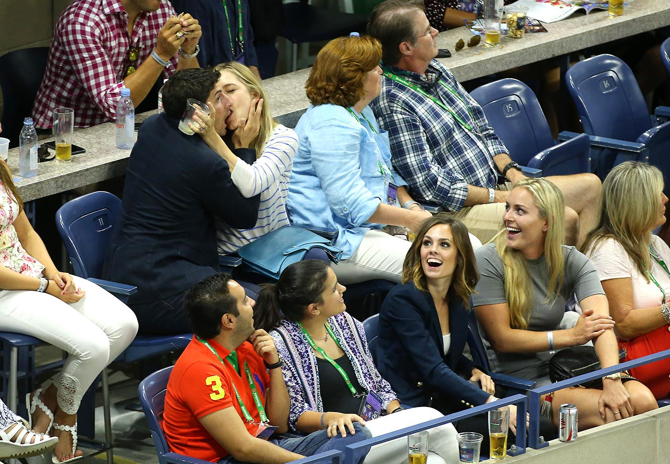 Jason Biggs and his wife, Jenny Mollen, playing it up for the U.S. Open 'kiss cam' while Lindsey Vonn (bottom right) laughs.