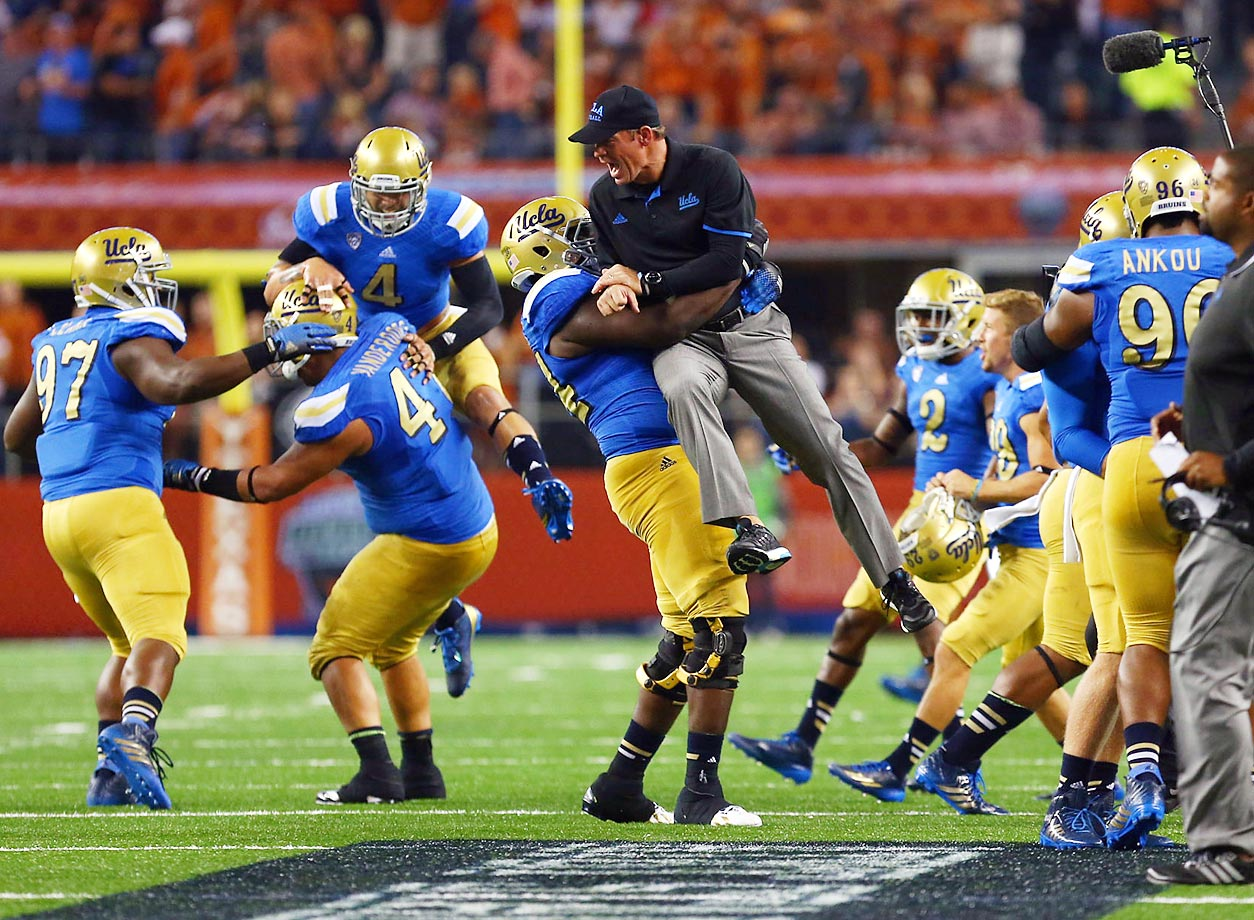 UCLA head coach Jim Mora celebrates with his players after their win over Texas.