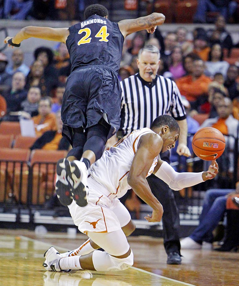 Texas forward Jonathan Holmes  tries to save a loose ball in front of Long Beach State guard Travis Hammonds.