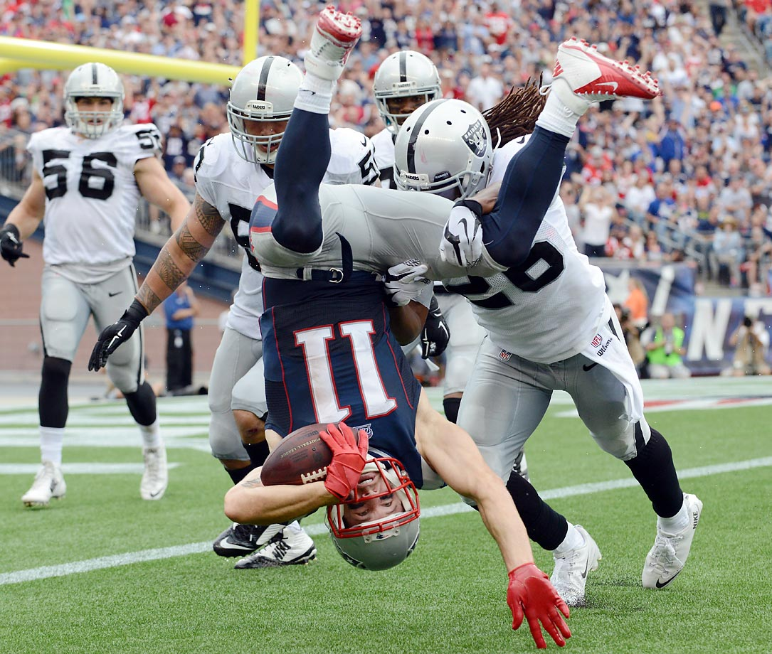 Wide receiver Julian Edelman of the New England Patriots is tackled by strong safety Usama Young of the Oakland Raiders.