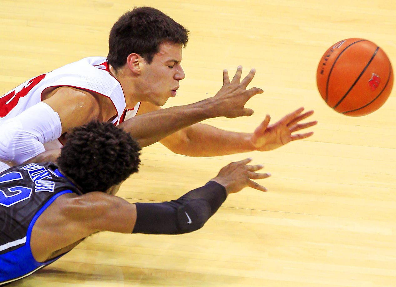 Duke's Justin Winslow and Wisconsin's Duje Dukan go after a loose ball.