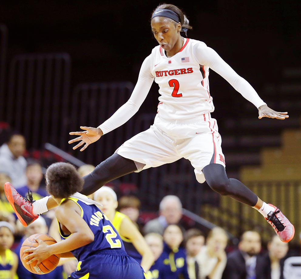 Rutgers defender Kahleah Copper leaps high to defend Michigan's Siera Thompson.