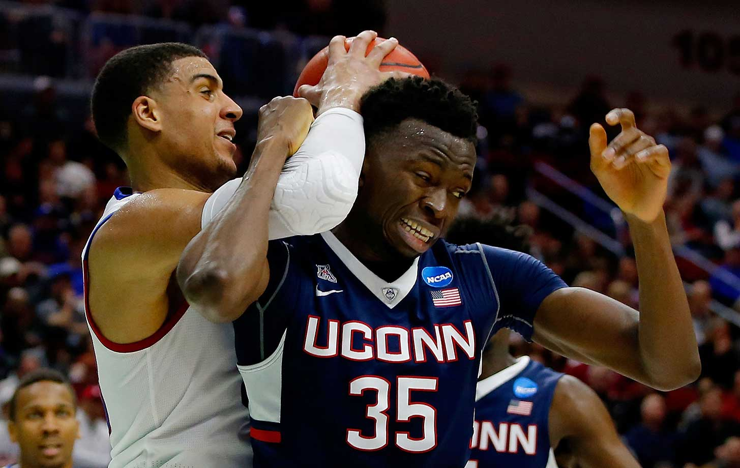 Landen Lucas of Kansas fouls Amida Brimah of Connecticut in a game in which the Jayhawks won 73-61.