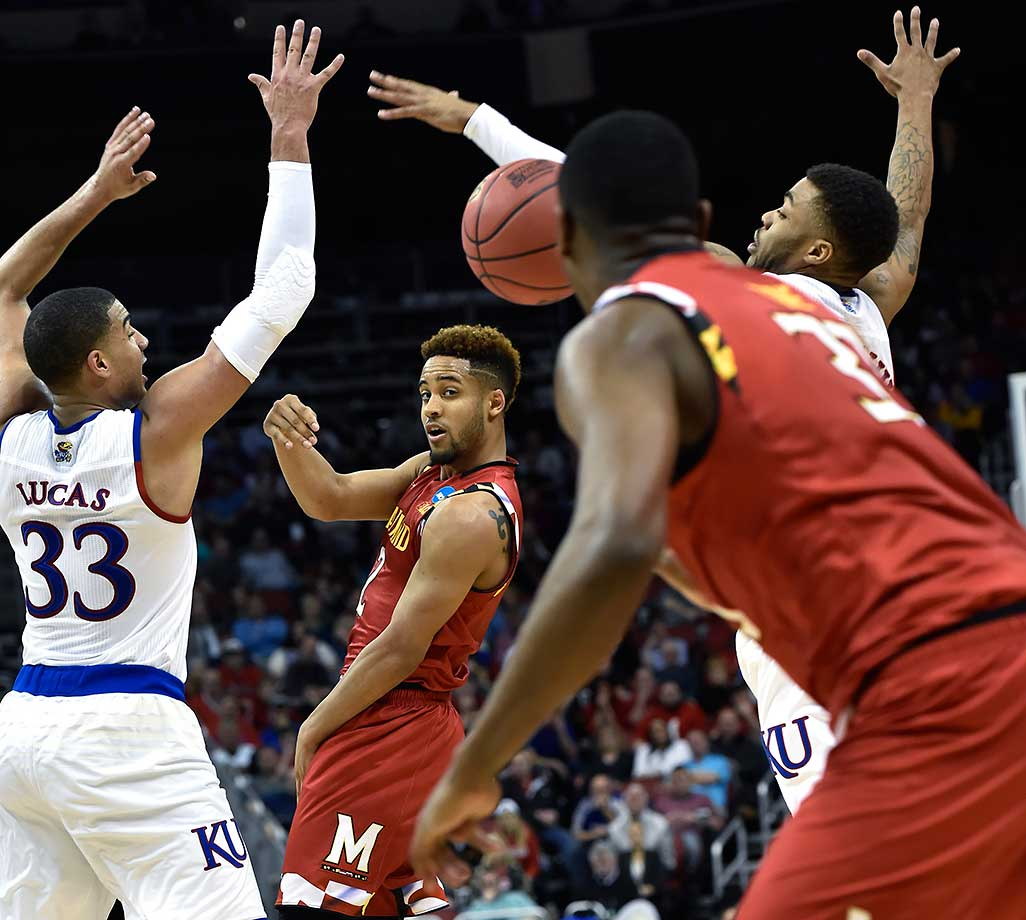 Maryland guard Melo Trimble passes between the defense of Landen Lucas (33) and guard Wayne Selden Jr. of Kansas.
