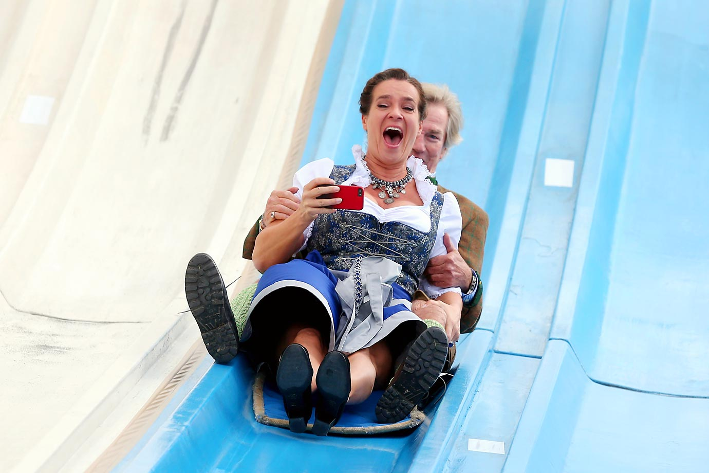 Katarina Witt with Prince Leopold von Bayern on a slide set up for Oktoberfest in Munich, Germany.