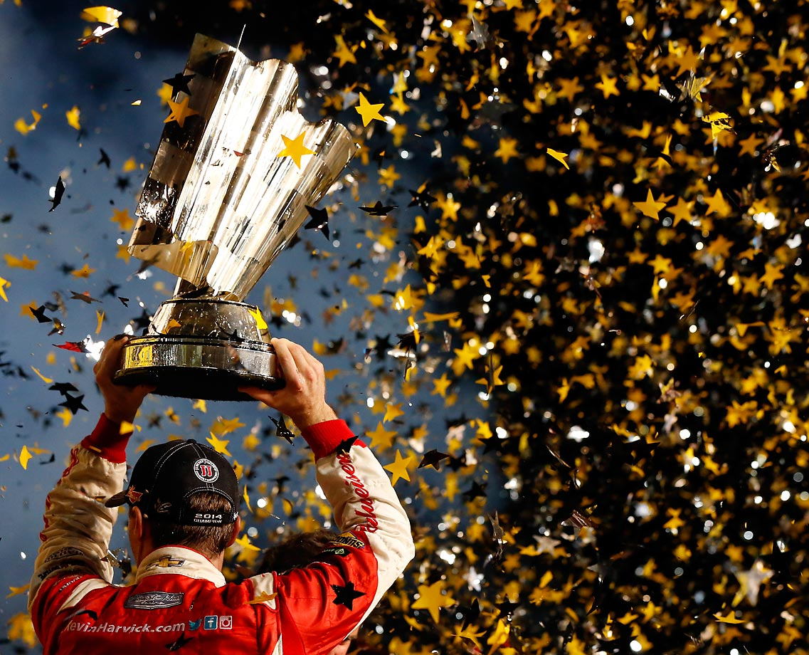 Kevin Harvick celebrates with the trophy in victory lane after winning during the 2014 NASCAR Sprint Cup season championship.