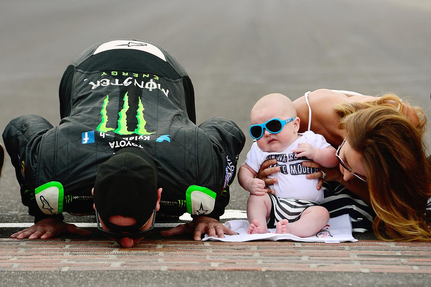 Kyle Busch and his wife Samantha celebrate by kissing the bricks as their son Brexton looks on.