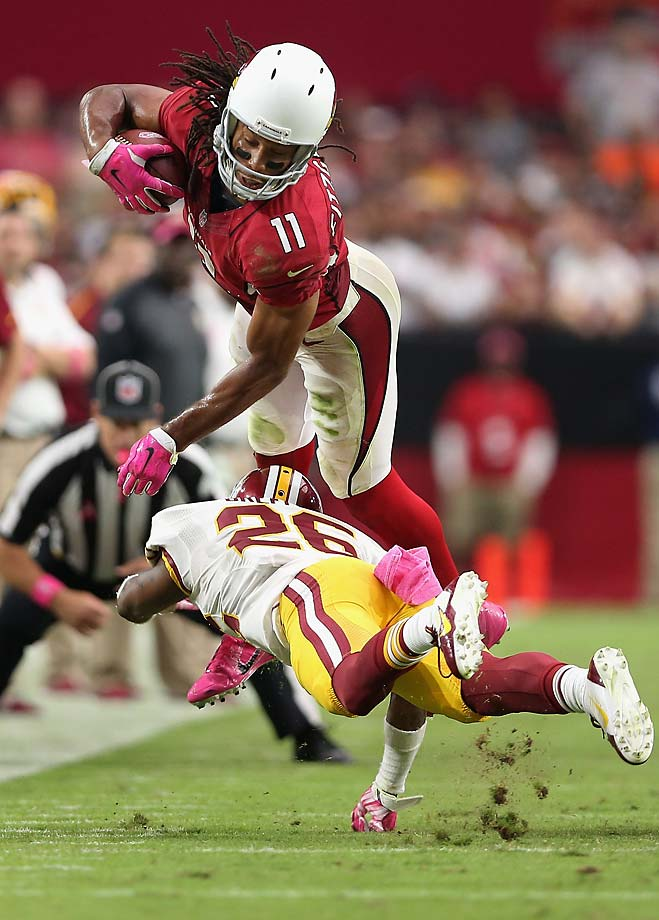 Larry Fitzgerald of the Arizona Cardinals leaps over strong safety Bashaud Breeland of the Washington Redskins after a reception during the fourth quarter.