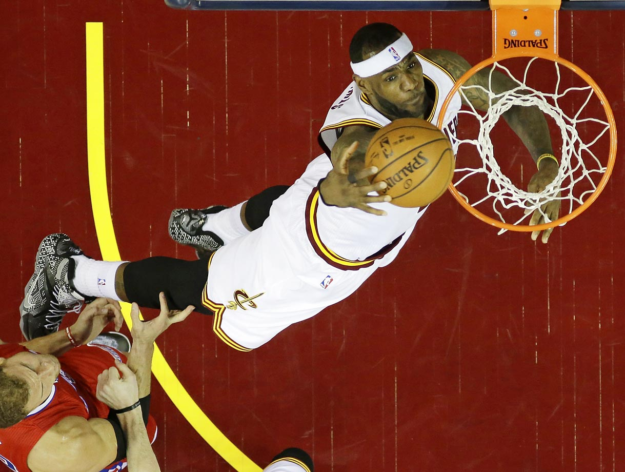 LeBron James dunks in front of Los Angeles Clippers forward Blake Griffin in Cleveland.