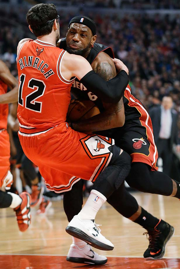LeBron James drives as Chicago Bulls guard Kirk Hinrich fouls him during a March 27, 2013, game in Chicago.