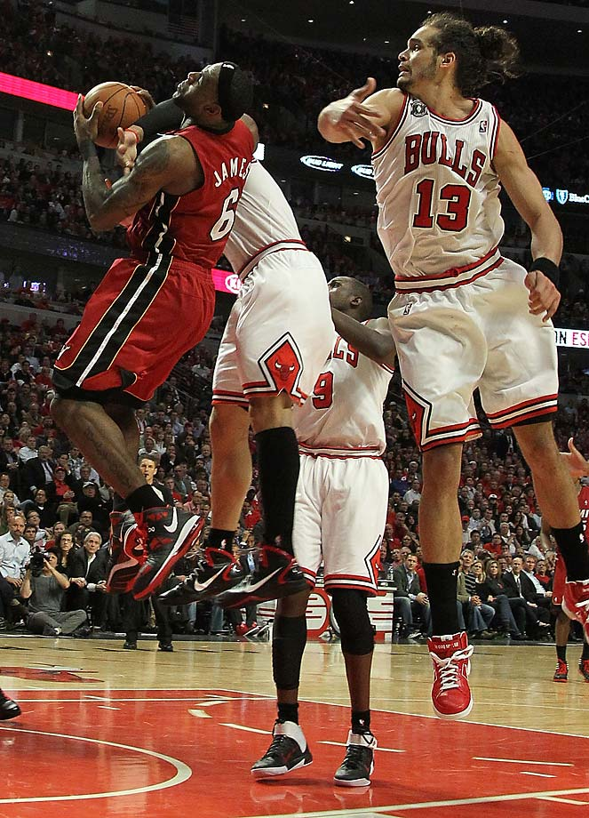 LeBron James is on the receiving end of a flagrant foul by Carlos Boozer of the Chicago Bulls as Joakim Noah also defends in Game 5 of the 2011 Eastern Conference Finals.