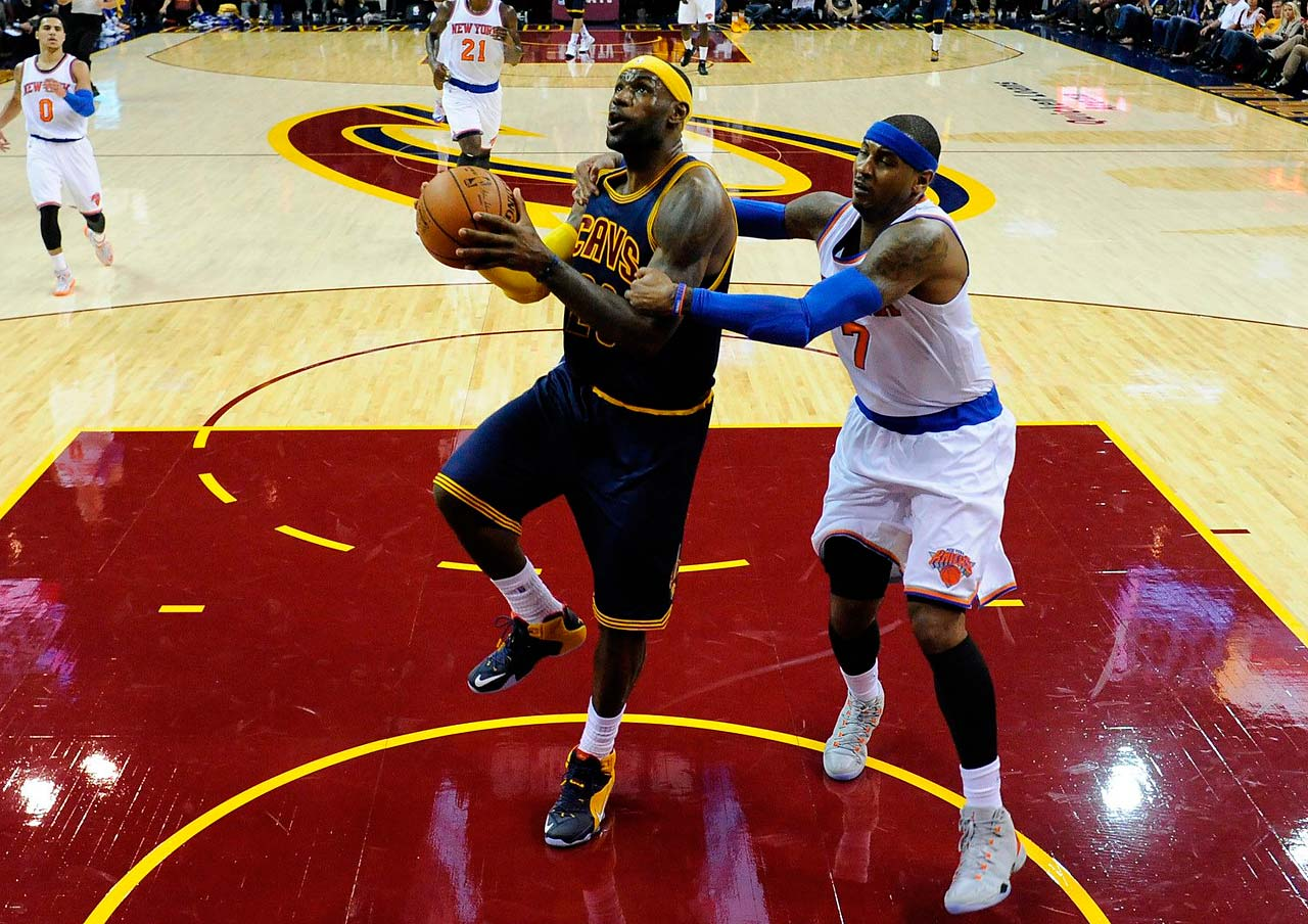 Carmelo Anthony fouls LeBron James during the 2014 season opener in Cleveland.