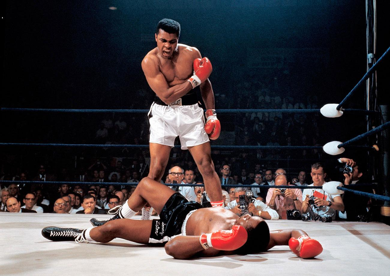Muhammad Ali stands over Sonny Liston after a successful knockout to retain the heavyweight title.