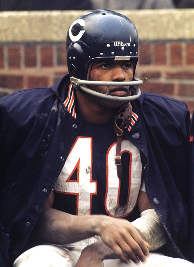 Chicago Bears running back Gale Sayers sits on the sidelines during a game at Wrigley Field against the Minnesota Vikings.
