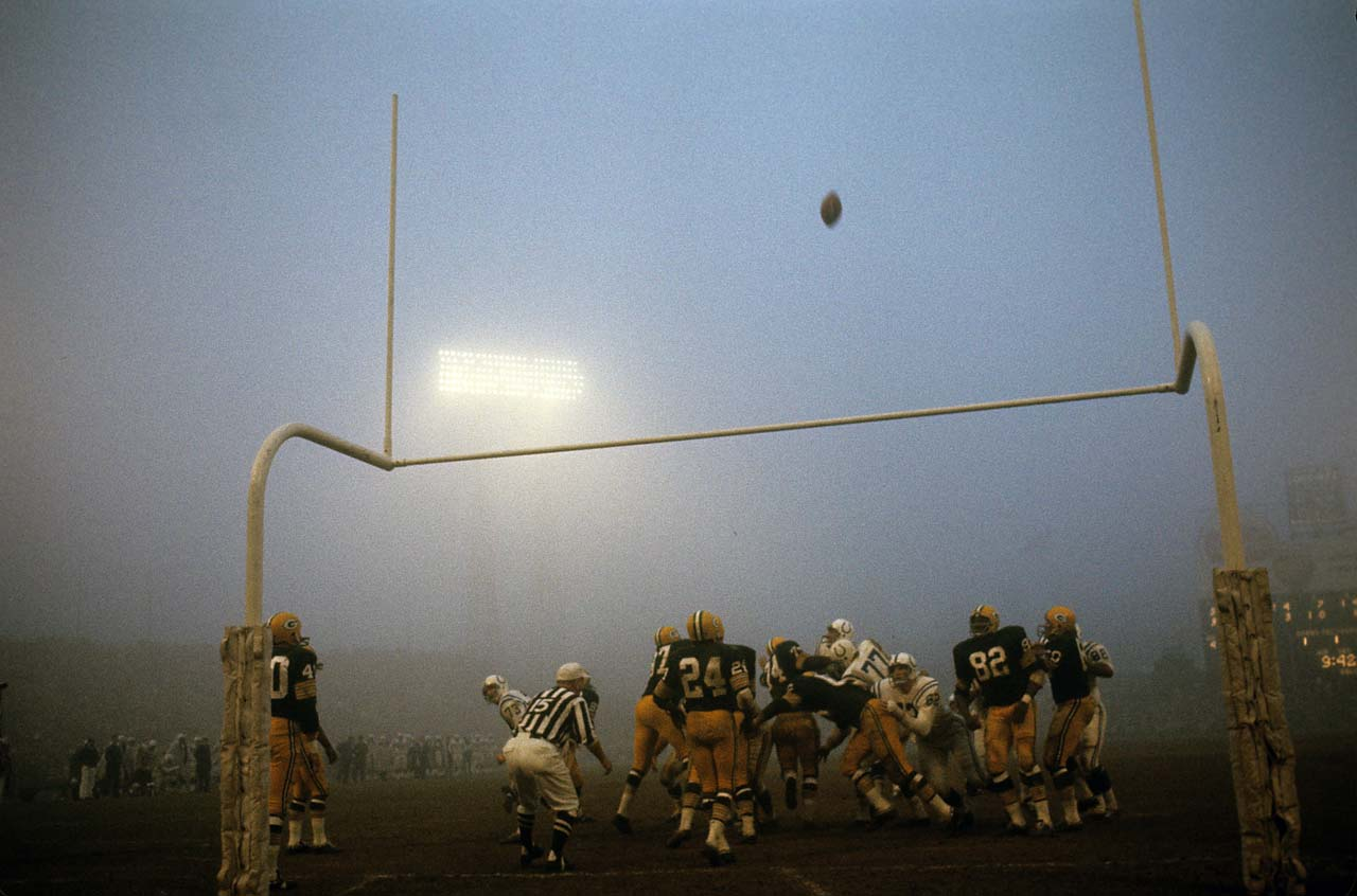 Green Bay Packers players watch a kick attempt by the Baltimore Colts during a foggy game at Memorial Stadium in Maryland.
