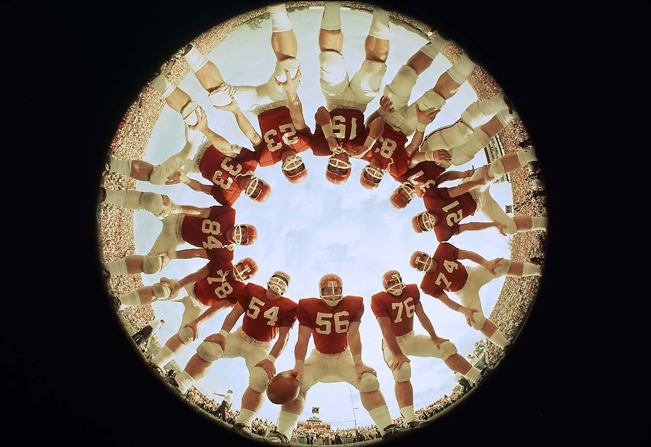Portrait of Arkansas offensive players (clockwise from bottom) Randy Stewart (56), Melvin Gibbs (54), Glen Ray Hines (78), Richard Trail (84), Bobby Burnett (33), Harry Jones (23), QB Jon Brittenum (15), Bobby Crockett (83), Robert Nix (37), Jim Lindsey (21), Dick Cunningham (74), and Mike Bender (76) posing in huddle before a game vs Texas at Razorback Stadium.