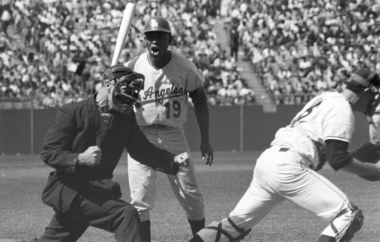 Los Angeles Dodgers' Jim Gilliam reacts angrily to a called third strike by Shag Crawford as the San Francisco Giants' Dick Bertell celebrates the team's win at Candlestick Park.
