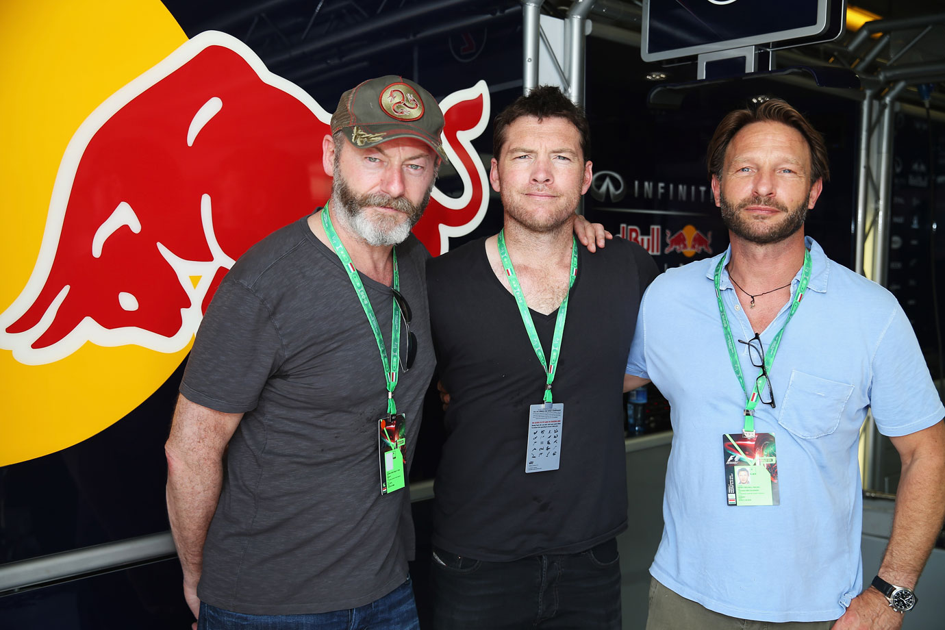 Liam Cunningham, Sam Worthington and Thomas Kretschmann pose together in the Infiniti Red Bull Racing garage following qualifying for the Hungarian Formula One Grand Prix at Hungaroring on July 27, 2013 in Budapest.