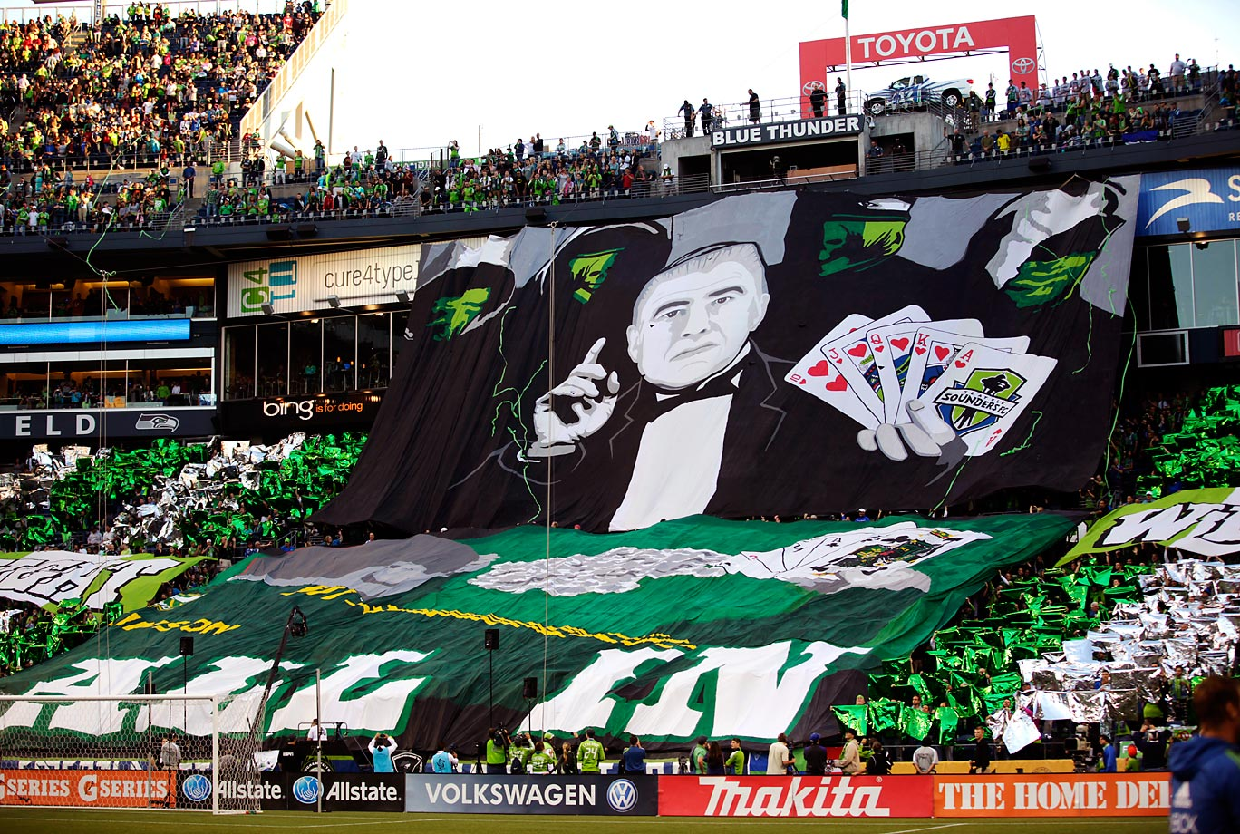 Seattle Sounders fans display their tifo that shows coach Sigi Schmid playing cards and holding a Royal Flush before a match against the Portland Timbers.