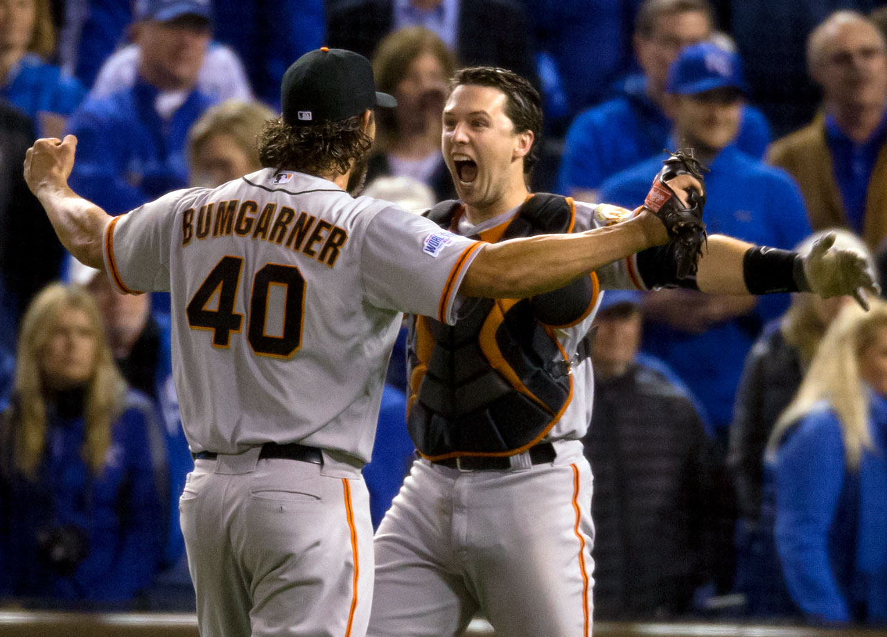 Madison Bumgarner and Buster Posey celebrate after the final out.  Bumgarner made his much-anticipated appearance out of the bullpen, throwing five innings on two days' rest to preserve a one-run lead, as the San Francisco Giants beat the Royals 3-2 in Kansas City.
