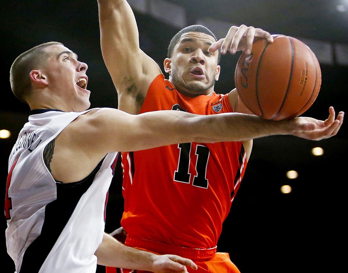 Oregon State's Malcolm Duvivier blocks a shot by T.J. McConnell of Arizona.