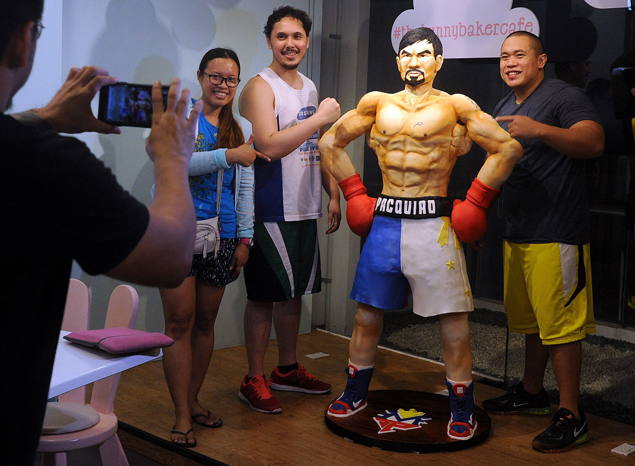 Customers take a picture with a life size 70 kilogram cake of Manny Pacquiao worth $4,000 at a cafe in Manila on May 2, 2015. The cake was made to commemorate the upcoming fight between Mayweather-Pacquiao fight. If Pacquiao had won, the cake would have be served free to customers.