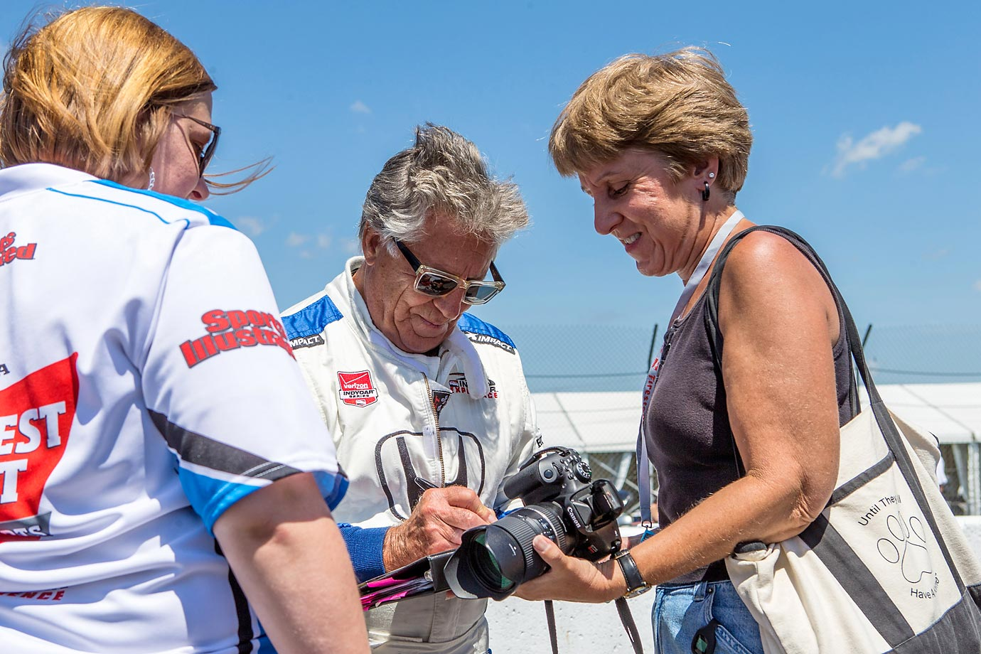 Mario Andretti signs an autograph for a fan before the Honda Indy 200 in Lexington, Ohio.