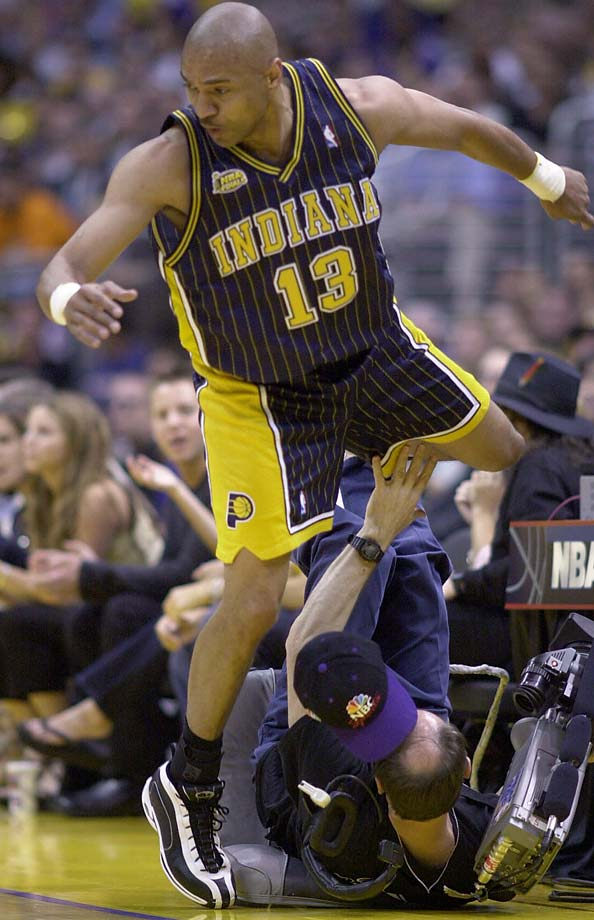 Mark Jackson dances over television cameraman Pat Rondou in Game 1 of the 2000 NBA Finals in Los Angeles.
