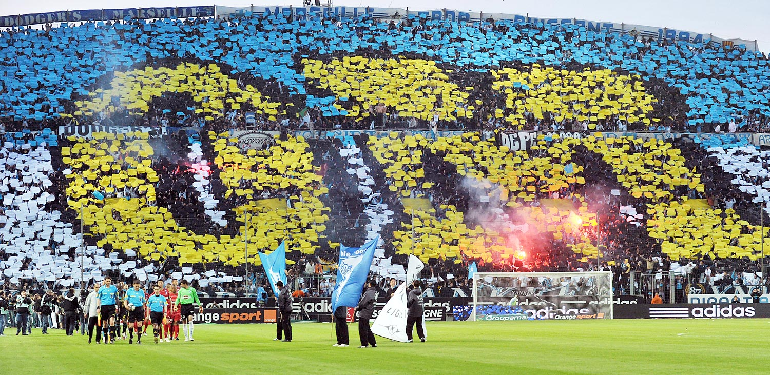 "Marseille's supporters use paper sheets to create an ""OM"" (Olympique de Marseille) tifo at the beginning of the French L1 football match between Marseille and Genoble."