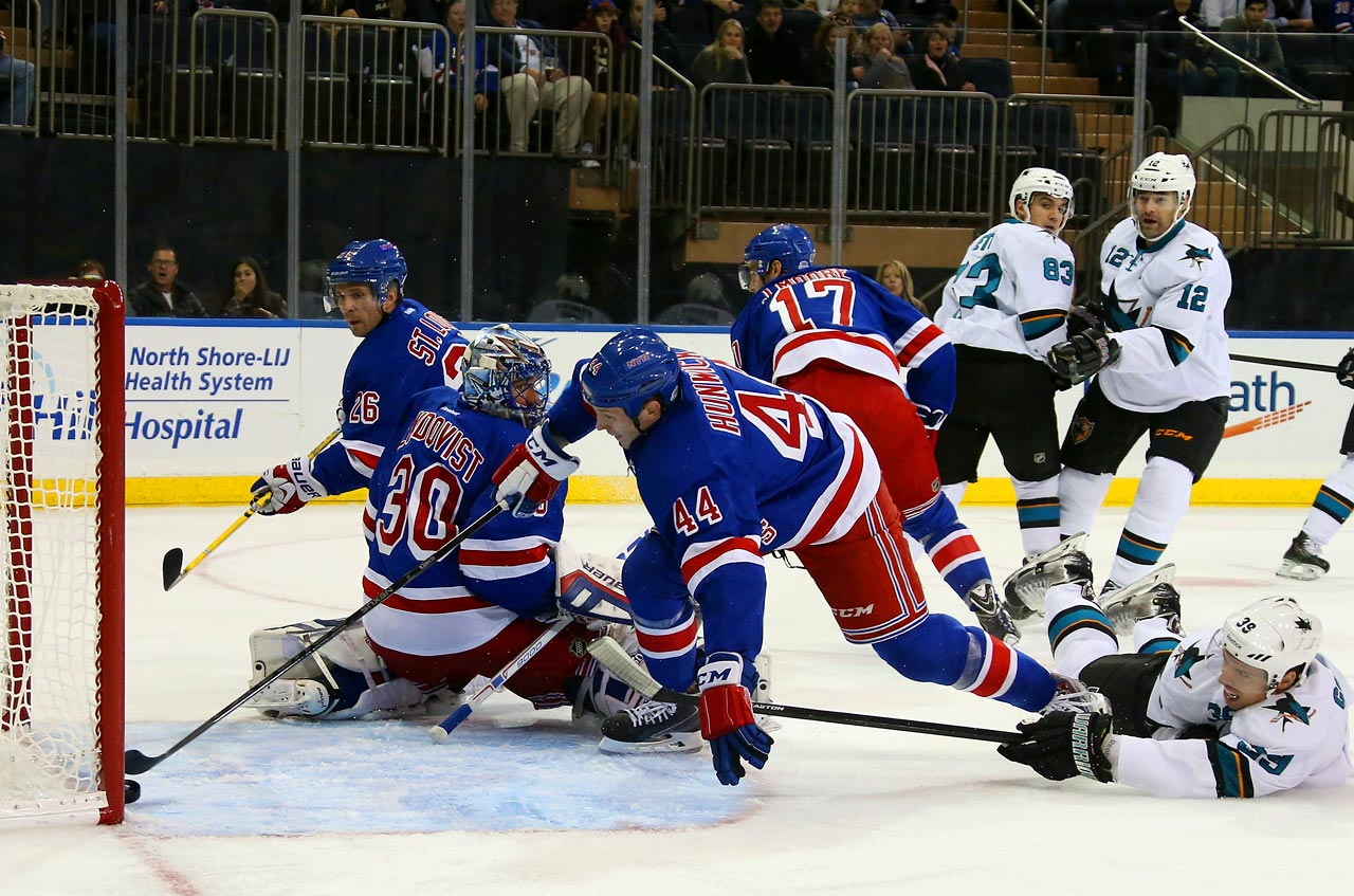 Rangers defenseman Matt Hunwick reaches to stop the puck from crossing the goal line as the Shark's Logan Couture hits the ice during a game at Madison Square Garden on Oct. 19.