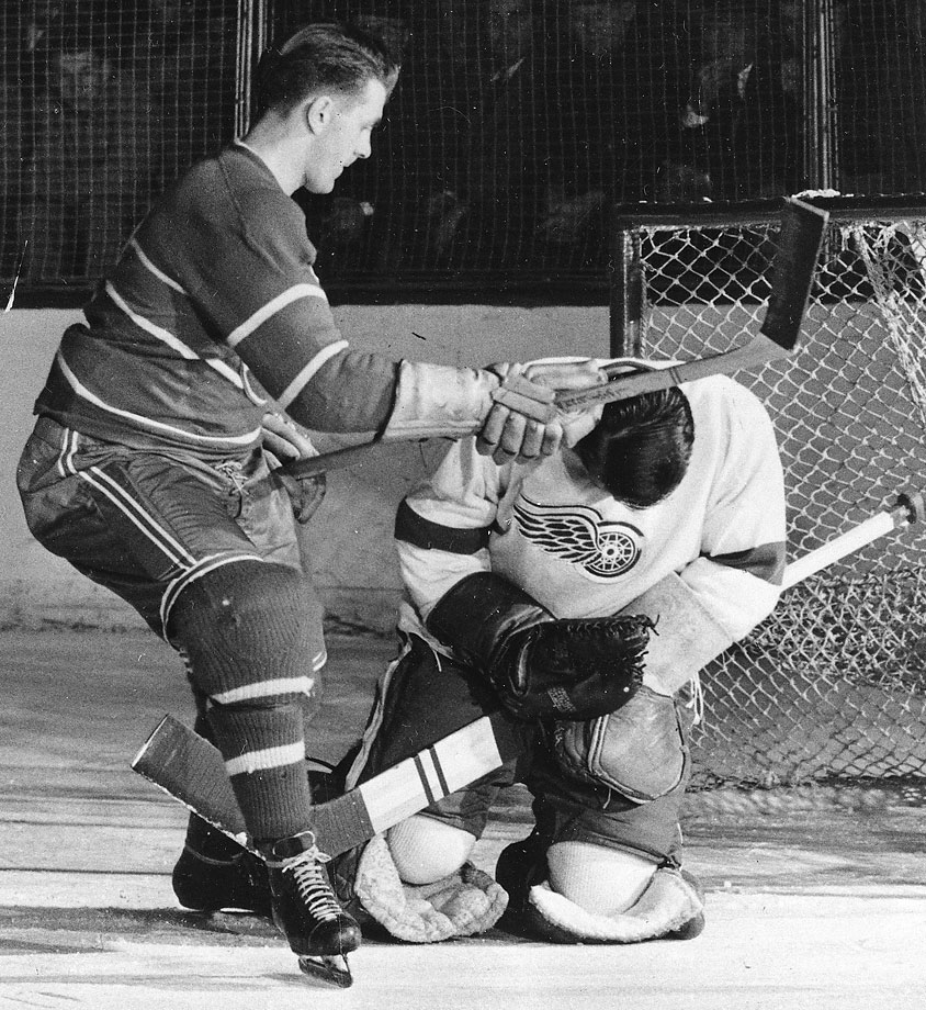 "The Rocket was a god to French-speaking Canadiens. When the Montreal Canadiens star was suspended at the tail end of the 1954 season—and for the entire '54 playoffs—after knocking out an official during a fight with the Boston Bruins, all of Quebec considered it a miscarriage of justice by Commissioner Clarence Campbell. There was rioting in Montreal, and when Campbell next appeared at the Montreal Forum he was pelted with debris, punched by an incensed fan and serenaded by thousands chanting ""A bas Campbell,"" (""Down with Campbell""). In this picture, Richard is delivering a blow to the head of Detroit goalie Terry Sawchuk in a 1950 game."