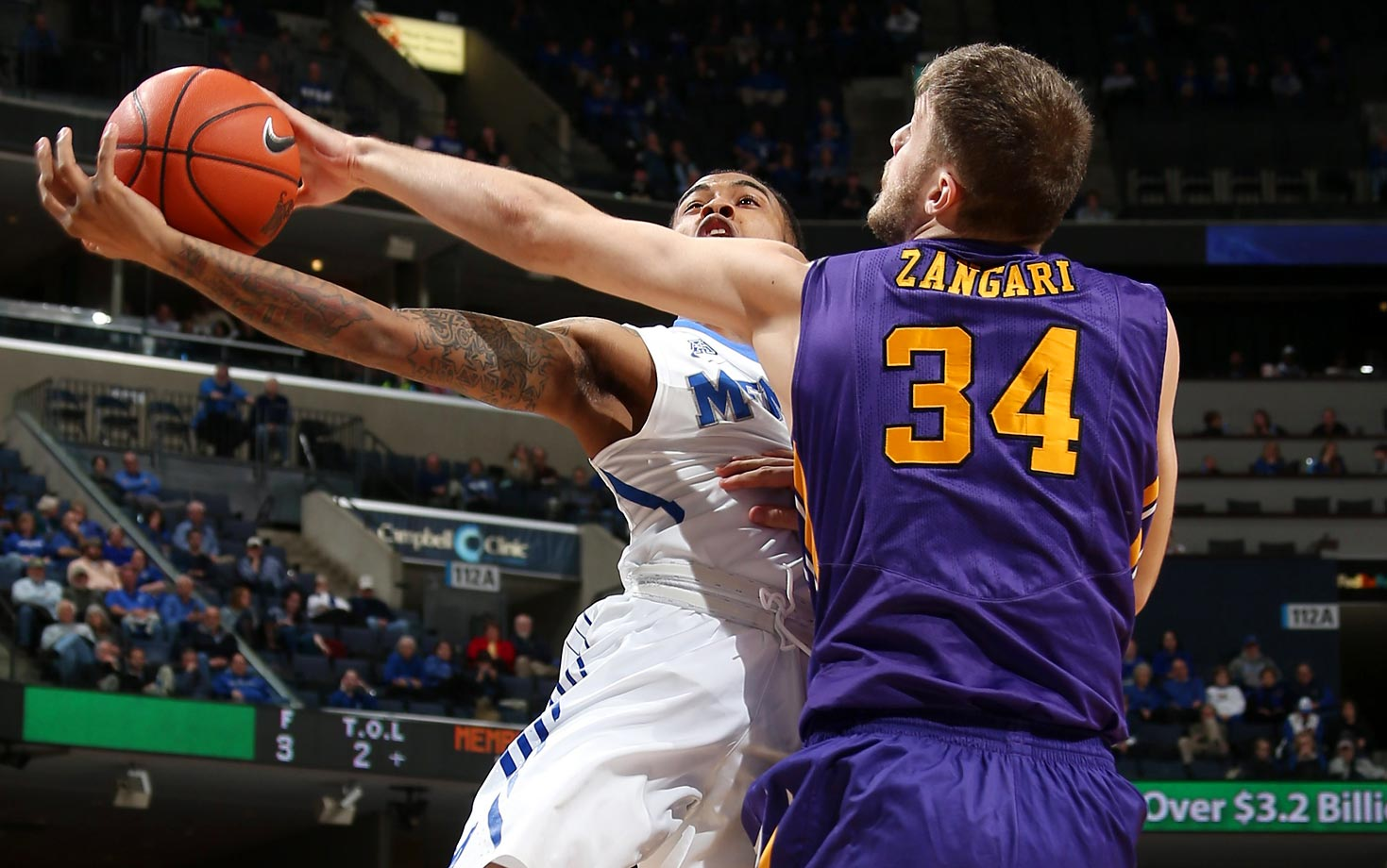 Michael Zangari of the East Carolina Pirates blocks a shot by D'Marnier Cunningham of Memphis. Memphis beat East Carolina 70-58.