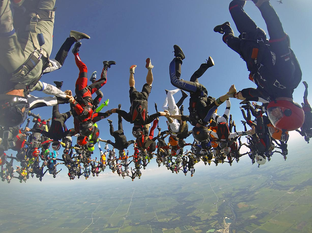 Members of an international team of skydivers join hands, flying head-down to build their world record skydiving formation. It took the team 13 attempts to to build the formation, resembling a giant flower, to beat the 2012 mark set by 138 skydivers.