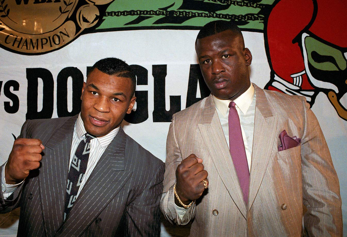 "Mike Tyson was just 23 and undefeated in 37 fights when he signed to defend his unified heavyweight title against lightly regarded James ""Buster"" Douglas. Even as the two posed at this press conference announcing their bout, most boxing fans were already looking forward to a hoped-for Tyson match-up with Evander Holyfield."