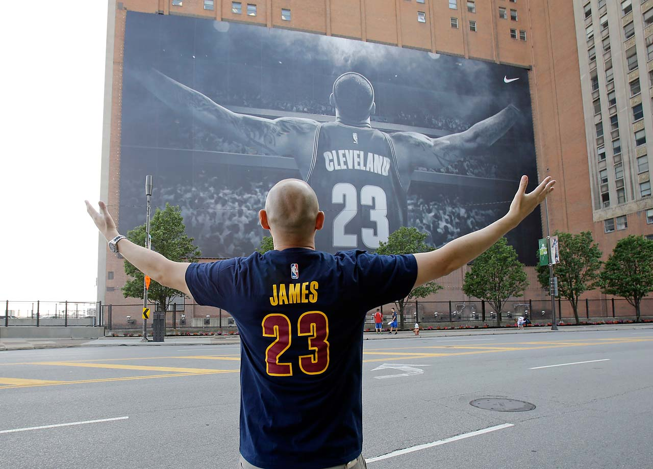A fan poses for a photo in front of a billboard featuring Cleveland Cavaliers forward LeBron James.
