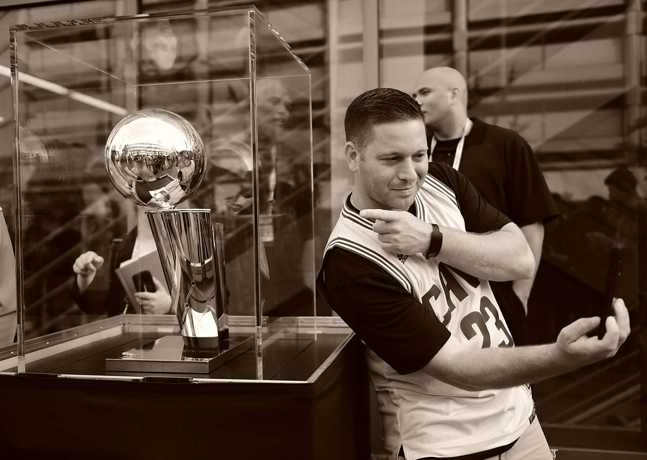 A fan posing with the championship trophy in Cleveland.